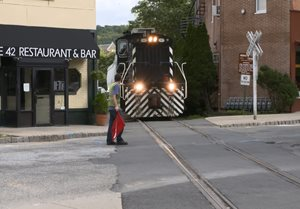 A train travels through downtown Dover, NJ while a flag man stops traffic.