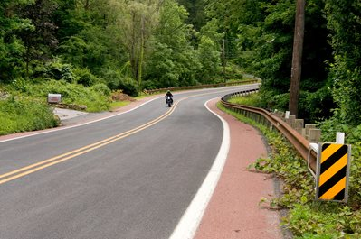 A motorcycle navigates a curve on a rural road.